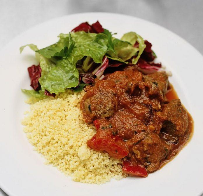 Cordero con una salsa a base de tomates, estilo mediterráneo, servido con cuscús.